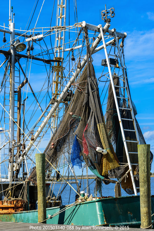 Blue, red, green and yellow fishing nets hang from a tangle of booms on a Gulf Coast fishing boat in color photo; 201503140-088