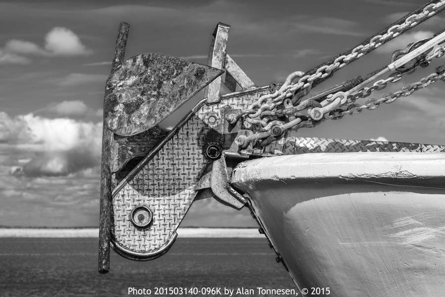 Anchor at the bow of fishing boat in Apalachicola, Florida with chains and ropes with blue water and sky in background in black and white photo 201503140-096K