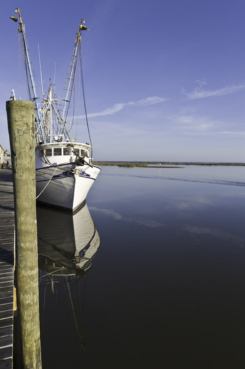 shrimp boats at wharf reflected in water